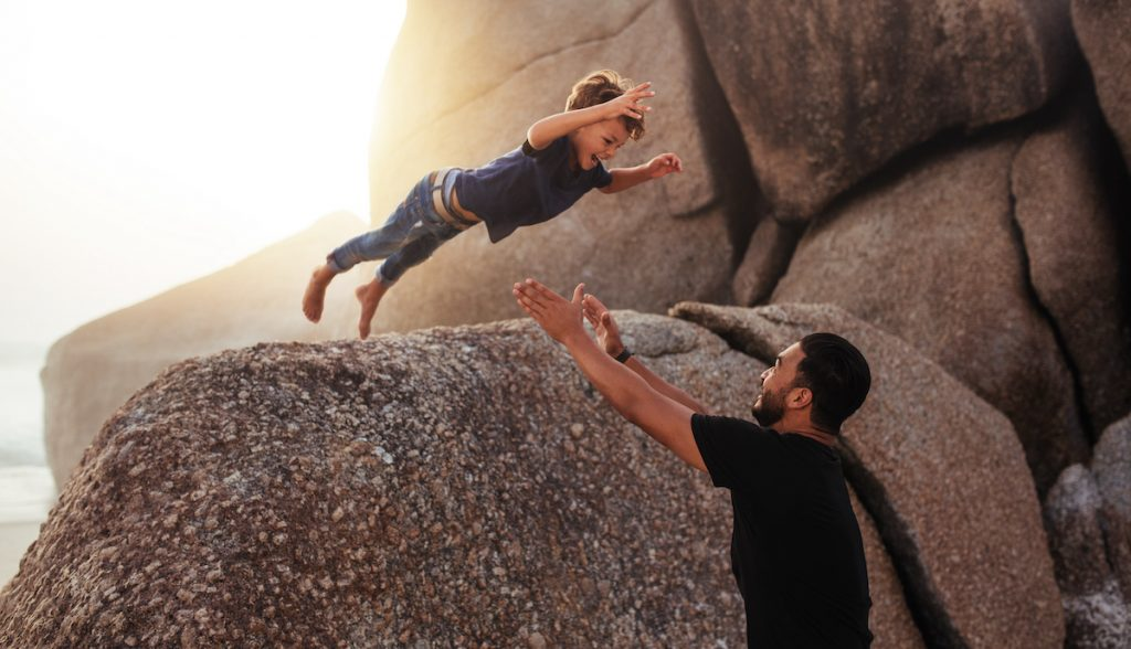 Man catching young son jumping into arms